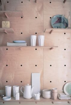 Plywood storage unit features detachable shelves and pegs, tailored for Airbnb…