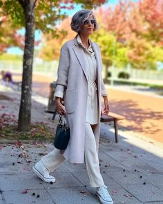 Long coat worn with tie waist top, pants and sneakers | Photo shared by Carmen Gimeno | For more style inspiration visit 40plusstyle.com