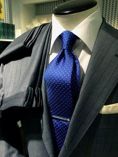 An electric blue tie is a great way to make a charcoal fabric suit like this stand out
