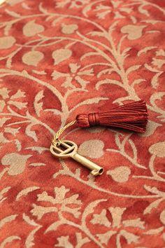 Salmon-Cinnabar color textile and tassel on a key; posted by Tina Motta via tumblr