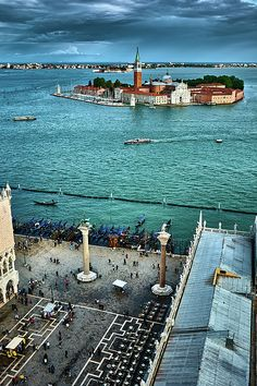 Scene in Venice. The Piazzetta di San Marco in the foreground, with its two large granite columns carrying symbols of the two patron saints of Venice, people visiting the Piazza and gondolas on the water, the San Giorgio Maggiore church in the background and the city behind it. This image is available for purchase as a ready to hang print as well as printed on other items. Click through the image to see your options! 30-days money back guarantee. Art for your life by Eduardo Jose Accorinti.