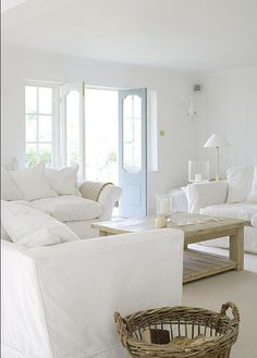 a lovely white living room with big sofas and glass doors .... my fav