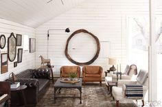 In the Art Barn, the Danish leather armchairs, bluestone cocktail table, and 18th-century Spanish wood ring are all from Lucca Antiques, and a pair of antique armchairs are covered in Belgian linen.    - ELLEDecor.com