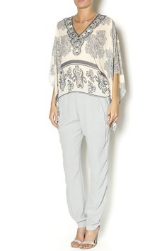 Printed poncho top with an asymmetrical hemline and an intricately beaded neckline. This light top will be a great addition to any outfit. Wear over a nude cami, white pants and sandals.