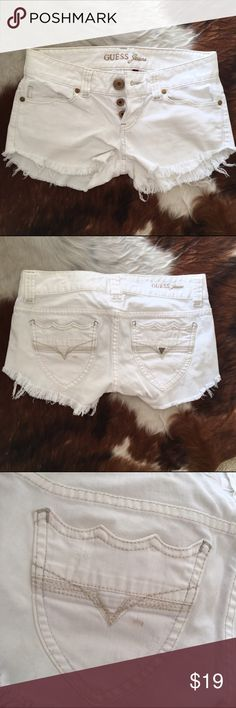 """Guess white denim shorts White denim. Low rise, distressed leg. Very stretchy. 3 button front, large back pockets. Flat measurements: 15 waist (these are LOW rise), 17 hip, 2"""" inseam. One dark mark that won't come out with washing on back pocket. Would model but they are way too tight fit like a 25. No trades please. Guess Shorts Jean Shorts"""