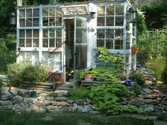 The rustic rock wall adds to this greenhouses' charm.