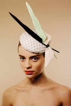 Lombardy | Awon Golding Millinery | Spring/Summer 2014 | Made from a hackle covered beret disc base draped with black veiling. Two goose feathers, one mint and one black, and a pinokpok bow add drama to the piece. It fastens to the head with elastic which fits snugly at the back of the head, and is hidden by the hair to give an invisible effect