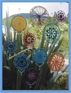"Made by Bethel of Bethania. ""My SunCatchers are basicly crocheted - using some doily patterns  others just progressed from my mind as I went along. I then crocheted them onto the thread wrapped metal rings, adding jewels to finish them off."""