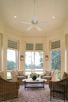 Sunroom with herringbone brick floor, wicker chairs with aqua sea cushions and tan buffalo check throw pillows - Architect: Historical Concepts