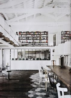 Like eceltic chairs around the table; collection of vases across far wall.  Upstairs books shelves and uneven upper floor panels