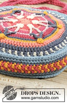 Crocheted bag with stripes, worked in the round from the centre and outwards. Piece is crocheted in DROPS Paris. Granny Square Häkelanleitung, Granny Square Crochet Pattern, Crochet Stitches Patterns, Crochet Round, Free Crochet Bag, Crochet Gratis, Crochet Purses, Crochet Cushions, Tapestry Crochet