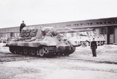 A repaired Jagdtiger moves out as a King Tiger with a Porsche turret sits at a maintenace facility