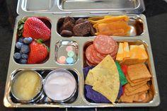 Strawberries, blueberries, Applesauce, yogurt, tortilla chips, wheat thins, cheese, pepperoni, dried mango & LeClerc probiotic cookies, 4 candies