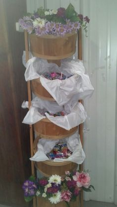 A tower of wooden buckets. Filled with candy and flowers