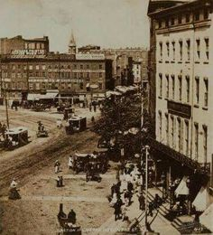 """1860s the intersection of Centre and Park Row. This area was the nexus of political and publishing. On the left (out of view) would be Tammany Hall, until 1868, headquarters for the Democratic political party machine.  The spire seen is that of St. Andrews Church and rises above the Tyron Row Buildings, topped by a sign that says """"Printer"""".  North of St. Andrews would be   5 Points. ephemeral"""