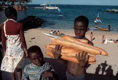Bruno Barbey View profile SENEGAL. Island of Goree, near Dakar. A boy carries French baguettes. 1980.