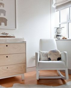 Love this nursery with calming neutral colours and a beautiful nursing chair.