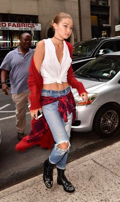 The sweltering temps in NYC this weekend didn't stop Gigi from embracing fall style. The model stepped out in a fuzzy red cardigan and distressed denim witha plaidflannel tied around her waist and black leather combat boots.