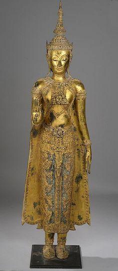 Bouddha paré et couronné, debout la main droite en abayamudra, geste du renoncement, la main gauche le long du pan déployé de sa robe monastique utarasanga richement ouvragé . Bronze laqué et doré. Royaume de Rattanakosin. Thaïlande.