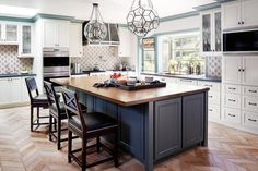 Gorgeous kitchen boasts two glass and iron faceted pendants illuminating a blue kitchen island topped with butcher block fitted with a small prep sink and hook and spout faucet lined with wood x back counter stools with navy leather nailhead seat cushions atop a brick herringbone floor.