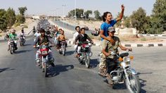 Residents of Tabqa city and Islamic State militants tour the streets in celebration after Islamic State militants took over Tabqa air base in northeast Syria, August 24, 2014.
