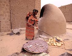 Woman baking bread in a clay oven. Most of the breads you could buy were laced with sand....it was inevitable!