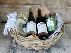 """Deze """"Puur genieten"""" mand bevat: 1 Woodwick kaars medium naar keuze. Deze geurkaars geeft door zijn brede houten lont een brede vlam en een zacht knapperend geluid zoals een open haard.  1 fles Kluisberg wijn """"Dornfelder"""" rood 75 cl. 1 fles Kluisberg wijn """"Pinot Gris"""" wit 75 cl. 1 handgemaakte hamamschaal Ottomania. 1 savon de Marseille zeep aan touw. 1 olijfzeepje 50 gr. Ottomania. 1 gastendoek Ottomania. 1 keukendoek van 100% linnen, bedrukt met een vervaagd au"""