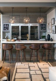 I love this bar and wine storage set up. Three Arteriors Beck Pendants illuminating a marble waterfall bar fitted with a wet bar sink and gold gooseneck faucet lined with wood counter stools. Basement Bar Designs, Home Bar Designs, Basement Ideas, Wet Bar Designs, Home Decor Kitchen, Kitchen Design, Rustic Basement, Cozy Basement, Walkout Basement