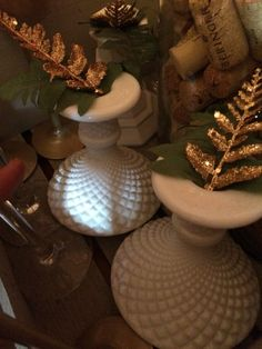 Green and gold fern tips in milk glass candle holders