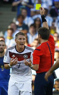 Germany's Bastian Schweinsteiger reacts as he is shown the yellow card by referee Nicola Rizzoli of Italy (R) during the 2014 World Cup final between Germany and Argentina at the Maracana stadium in Rio de Janeiro July 13, 2014. REUTERS/Kai Pfaffenbach