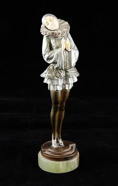 Paul Philippe. An Art Deco cold painted bronze and ivory figure modelled as a standing girl, in traditional costume, on a stepped circular base and onyx plinth, 8.25in.