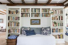Custom bookcases in a living room are stocked with tomes about boating and the sea. A mix of vintage and floral fabrics add visual interest to a crisp daybed. Click through for the full tour of this Sag Harbor home! | Lonny.com