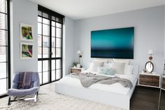 Loving how comfy this bed looks. Every room needs a statement piece like the art above the bed.