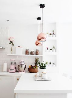 all white kitchen with rose gold pendants and pink accessories
