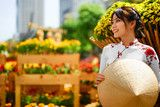 Photo: Culture Of Asia. Beautiful Happy Smiling Young Asian Woman Wearing Traditional White Ao Dai Dress ( Clothing ), Vietnamese Conical Hat ( Non La ) Leaf Hat In Flower Garden In Ho Chi Minh City, Vietnam