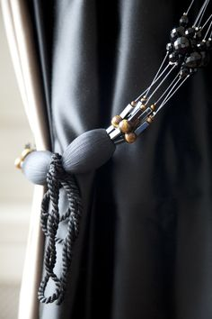 BEADED CLUSTER TIE-BAND Contemporary design composed of multi layered strands of exquisite jet crystal, hematite and tiger eye beads with bobbles covered in the finest silk