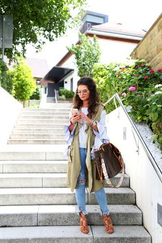FashionHippieLoves. Blue striped ruffle sleeves blouse+ripped fringed jeans+brown lace-up heeled sandals+khaki green long vest+Louis Vuitton tote bag. Summer Casual Outfit 2017