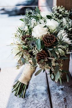 rustic winter wedding bouquet with white roses, eucalyptus and pine cones #winterwedding