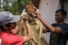 Dressing up: The Tiranda family put sunglasses on the mummy of Yohanes Tampang (centre) during the Ma'Nene ritual in Pangala Village, Toraja, held every three years