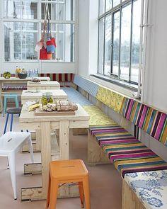 Een lange bank aan de muur, samen met losse kleine tafels, is superhandig omdat je gemakkelijk bij de bank kunt komen, de een rustig kan knutselen terwijl de ander werkt en omdat je met (stapelbare) krukjes zo veel zitplekken creëert als je wil.