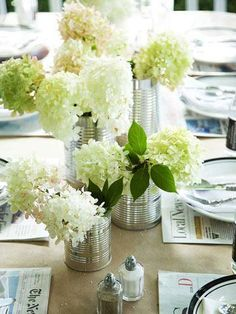 White hydrangeas look lovely in recycled cans. More summer decorating:  http://www.midwestliving.com/homes/outdoor-living/31-inspiring-outdoor-table-arrangements/