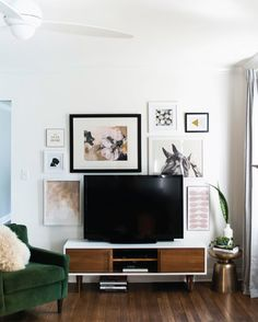 Incorporate your TV into a gallery wall. Plan out where your artwork will go in Photoshop, or play around with pieces of kraft paper (cut to the size of the frames) until you find an arrangement you like. Having some bigger pieces mixed in with smaller ones makes the wall look balanced, and having one big piece that's framed in black helps to tie it together with the TV itself.