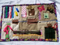 """Fidget Quilt  $55.00 (28""""w x 20""""l)  this quilt is good for Autism. A bead on a ribbon goes through 2  fabric tunnels,a belt velcro, button activity,beanie baby, lots of textured fabrics and items for Sensory Integration.  all items are attached"""