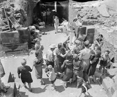 Hungry civilians of Catania scramble for rations being doled out by an RAF airman following the occupation of the city by the Allies on 5 August 1943. Victor Sierra
