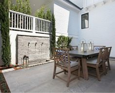 Backyard Patio with zinc top table, teak chairs, natural stone flooring and water feature. #Patio Spinnaker Development.