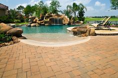 Gorgeous pool backyard with beautiful pavers, beach entrace, and waterfall...