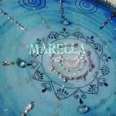 Mandala em aquarela com tons de azul e prata, detalhes em pastilhas de vidro. Diâmetro médio de 25cm. Moldura padrão branca.