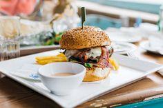 Juicy burger in a vibrant interior - FoodiesFeed