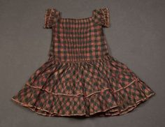 Circa 1850 coral and green plaid taffeta short-sleeved dress with ruched front bodice and bias cut flounced skirt. Via Fine Arts Museums of San Francisco.