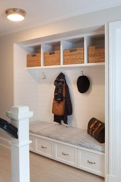 A recessed mudroom alcove is filled with a built-in bench fitted with four with drawers tucked four coat hooks lining a shiplap wall accented with overhead shelves filled with woven bins.